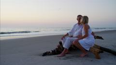 Loving mature Caucasian couple sharing kiss on ocean beach at sunrise Stock Footage