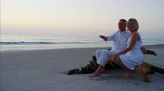 Loving Caucasian seniors on the ocean beach at sunset Stock Footage