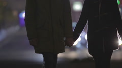 Two people in love holding hands, walking slowly along busy city street at night Stock Footage