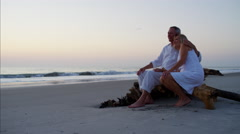 Happy senior Caucasian couple relaxing on their beach holiday at sunset Stock Footage