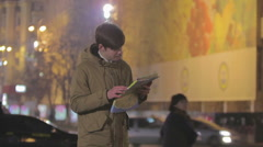 Young man lost in big city, looking at map, asking passer-by to show right way Stock Footage