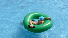 boy on the buoy in pool - stock footage