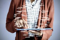 Businesswoman using a tablet against sphere of skills Stock Photos