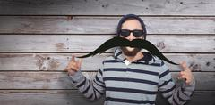 Portrait of happy hipster wearing sunglasses against artificial mustache Stock Photos