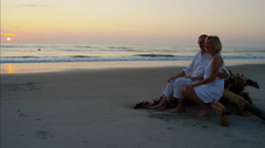 Caucasian seniors in bright clothing on resort beach at sunrise Stock Footage