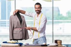 Young tailor working on new clothing design - stock photo