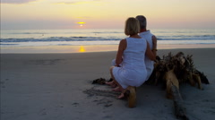 Happy senior Caucasian couple relaxing on their beach holiday at sunrise Stock Footage