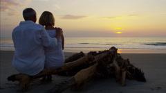 Happy Caucasian seniors on the ocean beach at sunset Stock Footage
