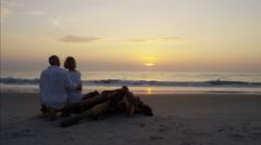 Loving Caucasian seniors on their beach vacation at sunrise Stock Footage