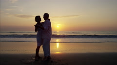 Silhouette of mature Caucasian couple dancing on the ocean beach at sunrise Stock Footage