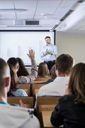 Activating his students during a lecture on economy Stock Photos