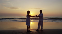 Silhouette of mature Caucasian couple dancing on the beach at sunrise Stock Footage