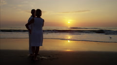Silhouette of Caucasian seniors dancing on the ocean beach at sunset Stock Footage