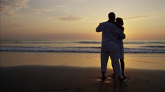 Silhouette retired Caucasian couple dancing on the beach at sunset Stock Footage