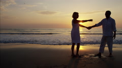 Silhouette of healthy Caucasian seniors dancing on the beach at sunset Stock Footage