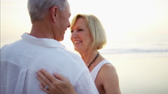 Senior Caucasian couple in bright clothing dancing at their beach holiday resort Stock Footage