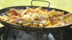 Roasted potatoes with onion and rosemary in a cast iron pan grill Stock Footage