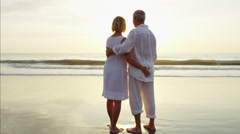 Healthy senior Caucasian couple sharing kiss on beach vacation at sunset Stock Footage