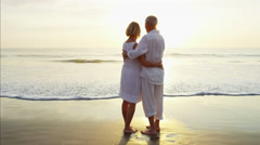 Senior Caucasian couple holding hands and kissing on the beach at sunset Arkistovideo