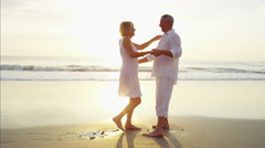 Healthy senior Caucasian couple dancing at their beach resort at sunset Stock Footage