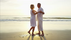 Loving Caucasian seniors dancing together on the beach at sunset Stock Footage