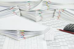 House and pile paperwork of report with colorful paperclip - stock photo