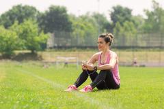 Athlete girl sitting grass phone listening headphones Stock Photos