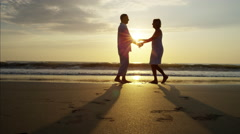 Silhouette of senior Caucasian couple dancing on their beach holiday at sunrise Stock Footage