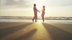 Silhouette of mature Caucasian couple dancing on the beach at sunset Stock Footage