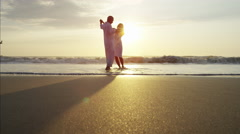 Silhouette of loving Caucasian seniors dancing together on the beach at sunrise Stock Footage
