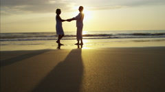 Silhouette of loving Caucasian seniors dancing together on the beach at sunset Stock Footage