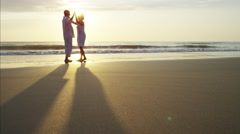 Silhouette of retired Caucasian couple dancing on the ocean beach at sunset Stock Footage