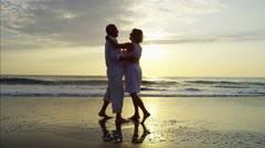Silhouette of carefree senior Caucasian couple dancing on the beach at sunrise Stock Footage
