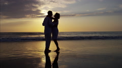 Silhouette of Caucasian seniors dancing together on the beach at sunset Stock Footage
