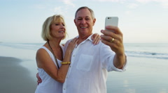 Loving mature Caucasian couple in white clothing taking selfie on the beach Stock Footage