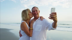 Happy Caucasian seniors taking selfie and sharing kiss on their beach holiday Stock Footage