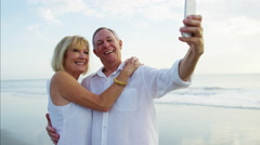 Loving mature Caucasian couple having fun taking selfie on the beach Stock Footage
