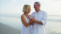 Smiling senior Caucasian couple taking selfie on mobile on the beach resort Stock Footage