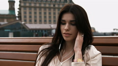 Young beautiful brunette woman listening to music with phone sitting on a bench - stock footage