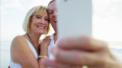 Loving Caucasian seniors taking selfie on smart phone on the beach resort Stock Footage