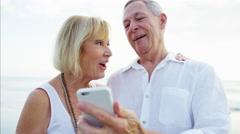 Caucasian seniors using smart phone technology on their beach vacation Stock Footage