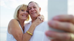 Happy retired Caucasian couple in white clothing taking selfie on the beach Stock Footage