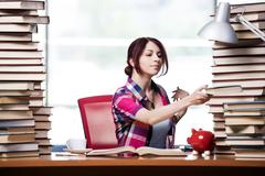 Concept of expensive textbooks with female student - stock photo