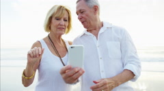 Loving mature Caucasian couple taking selfie on smartphone at beach resort Stock Footage
