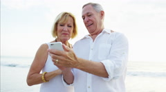 Happy Caucasian seniors using smartphone technology on the beach vacation Stock Footage