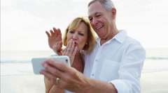 Carefree senior Caucasian couple smiling for video diary on the beach Stock Footage