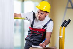 Delivery man taking dimensions with tape measure - stock photo