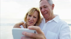 Happy retired Caucasian couple smiling for video diary on the beach Stock Footage
