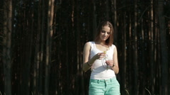 Portrait of beautiful girl in pine forest among flowers Stock Footage