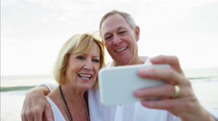 Loving mature Caucasian couple making video diary on the beach Stock Footage